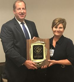 Jane N. Hinson, MS, BSN, RN, Health Director of the Iredell County Public Health Department, presents the public health award to Rhett Melton, CEO for Partners Behavioral Health Management